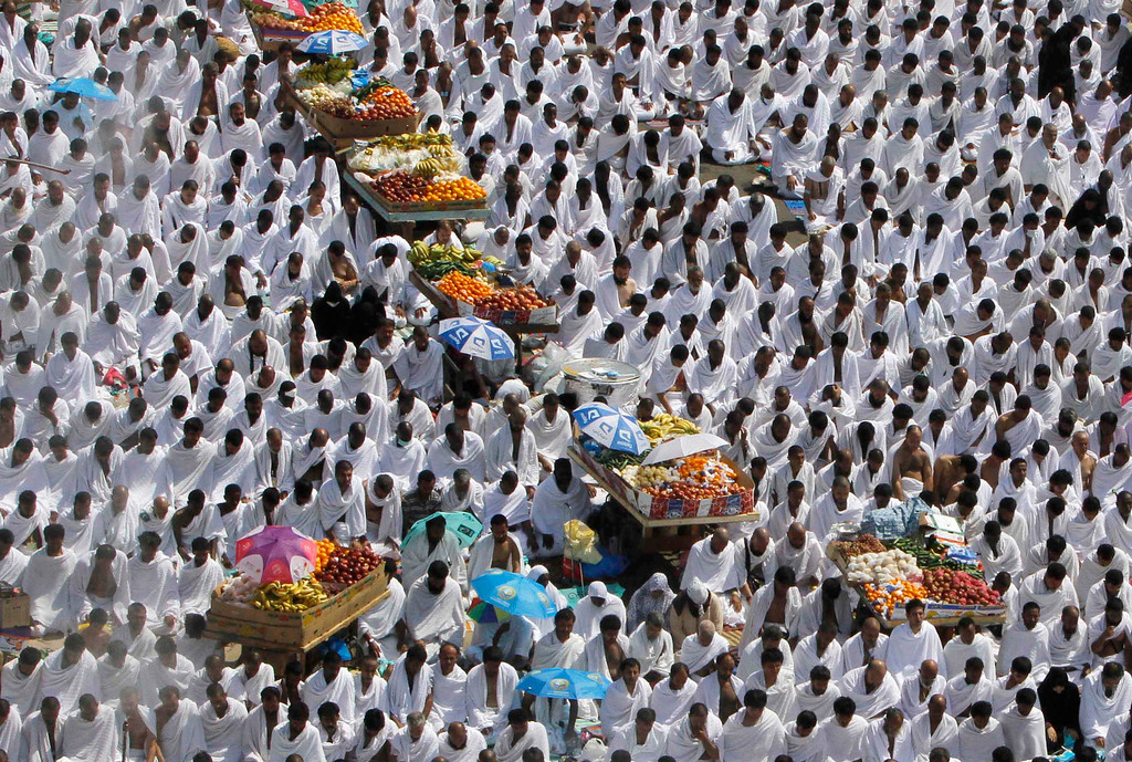 . Muslim pilgrims pray the noon prayers near fruit carts in Arafat, near the holy city of Mecca, Saudi Arabia, Monday, Oct. 14, 2013. As part of the hajj, or pilgrimage, the faithful head to a hill called Jabal al-Rahmah, meaning Mountain of Mercy, about 20 kilometers (12 miles) east of Mecca, that Muslims believe the Prophet Muhammad called on people to abolish their feuds and put aside their racial, economic and tribal differences. (AP Photo/Amr Nabil)
