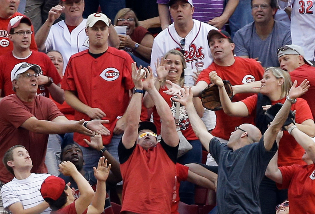 . A fan catches a three-run home run hit by Cincinnati Reds\' Xavier Paul off Colorado Rockies\' Jon Garland in the first inning of a baseball game, Wednesday, June 5, 2013, in Cincinnati. (AP Photo/Al Behrman)
