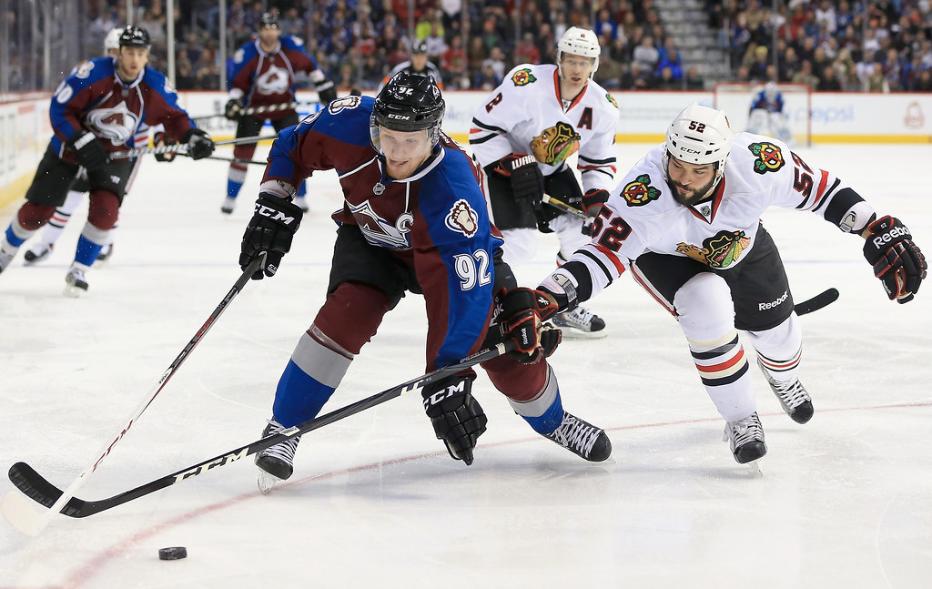 . Gabriel Landeskog #92 of the Colorado Avalanche controls the puck against Brandon Bollig #52 of the Chicago Blackhawks at the Pepsi Center on March 18, 2013 in Denver, Colorado.  (Photo by Doug Pensinger/Getty Images)