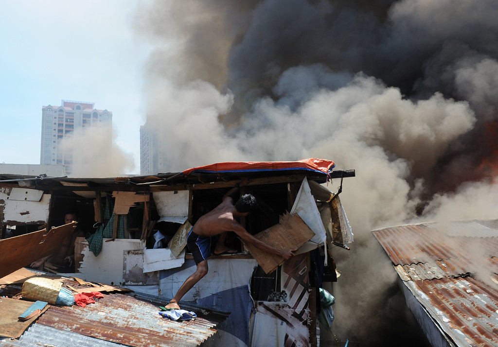 . A resident destroys a wall of his house in an effort to salvage belongings as a fire engulfs a shanty town in the financial district of Manila on July 11, 2013, leaving more than 1,000 people homeless according to city officials. There were no immediate reports of casualties from the blaze, which occurred mid-morning amid government plans to relocate thousands of families living in areas vulnerable to floods and typhoons. TED ALJIBE/AFP/Getty Images