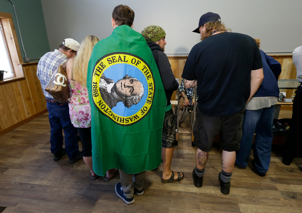 . Brian Travino, a student at Western Washington University wears a Washington state flag, as he waits with other customers to purchase recreational marijuana at Top Shelf Cannabis, Tuesday, July 8, 2014, in Bellingham, Wash., in the first half-hour of legal sales in the state. (AP Photo/Ted S. Warren)