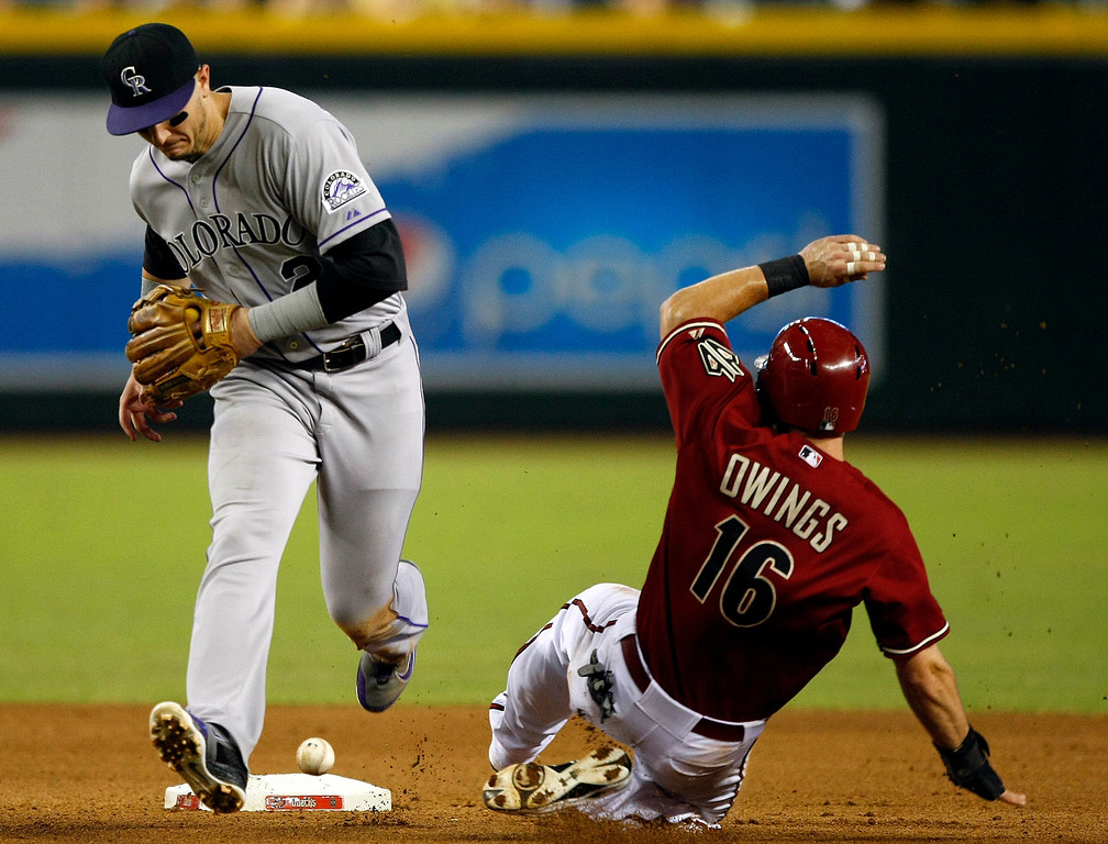 . Colorado Rockies shortstop Troy Tulowitzki, left, commits an error while trying to turn a double play as Arizona Diamondbacks\' Chris Owings (16) slides safely into second base in the fourth inning during a baseball game on Sunday, Sept. 15, 2013, in Phoenix. The Rockies scored a run on the play. (AP Photo/Rick Scuteri)