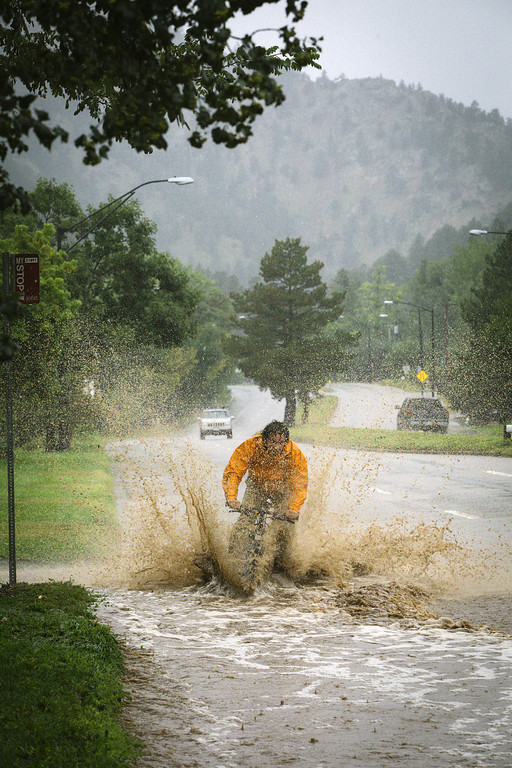 . BOULDER, CO - SEPTEMBER 12: Pro mountain biker Joey Schusler tests his skills along Canyon Boulevard September 12, 2013 in Boulder, Colorado. An estimated 6-10 inches of rain fell in 12-18 hours and more is expected throughout the day. Flash flood sirens warned people to stay away from Boulder Creek and seek higher ground.  (Photo by Dana Romanoff/Getty Images)
