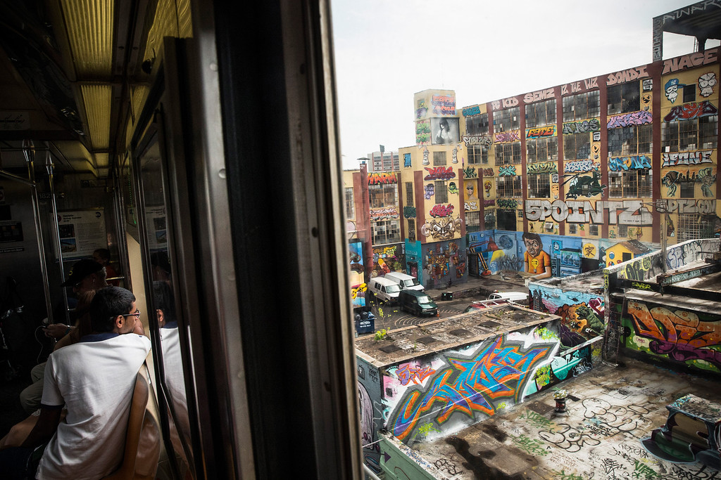 ". NEW YORK, NY - AUGUST 09:  The ""5 Pointz\"" building is seen from a passing subway car on August 9, 2013 in the Long Island City neighborhood of the Queens borough of New York City. 5 Pointz is a series of properties that graffiti artists use as an outdoor art exhibit space - it is considered the Mecca of the graffiti world. The space has been used as a space for graffiti artists since the early 1990s, though in 2011, Jerry Wolkoff, the owner of the property, announced he planned to demolish the building to build high-rise residential buildings. The 5 Pointz graffiti community has since been in a battle to keep the space as is; they are currently petitioning the government to consider the space a protected cultural landmark.  (Photo by Andrew Burton/Getty Images)"
