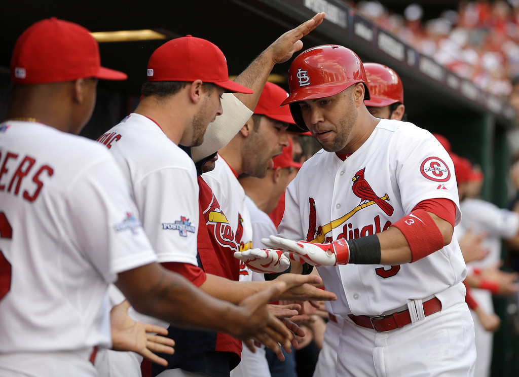 . St. Louis Cardinals\' Carlos Beltran, right, is congratulated in the dugout by teammates after hitting a three-run home run against the Pittsburgh Pirates in the third inning of Game 1 of baseball\'s National League division series on Thursday, Oct. 3, 2013, in St. Louis. (AP Photo/Jeff Roberson)