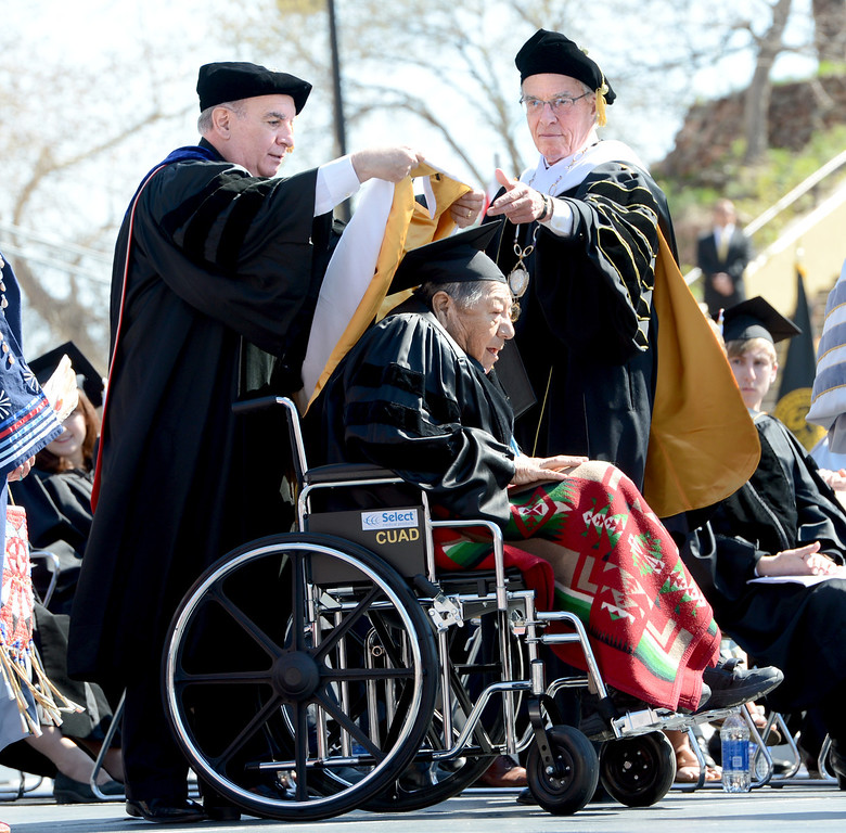 . Chancellor Phil DiStefano, left, and President Bruce Benson, award an honorary degree to  Gerald One Feather  during the 2013 University of Colorado Spring Commencement on Friday. (Cliff Grassmick/Daily Camera)