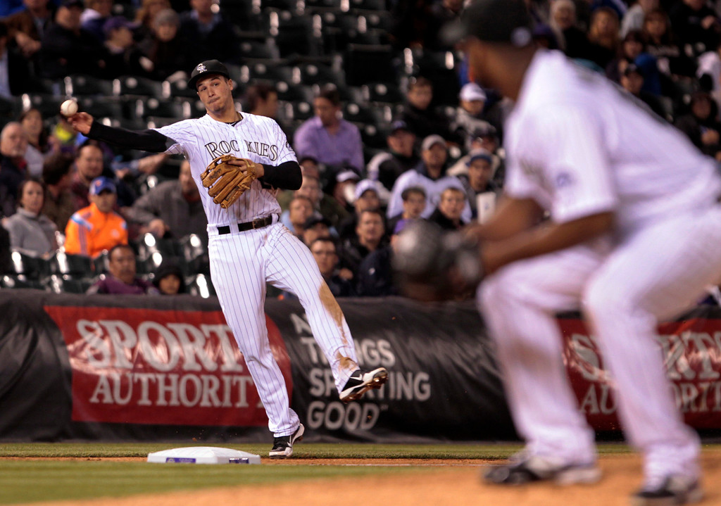 . Colorado Rockies third baseman Nolan Arenado, left, throws to first base to put out New York Mets\' David Right (not shown) at first base in the seventh inning of a baseball game in Denver, Thursday, May 1, 2014. (AP Photo/Joe Mahoney)