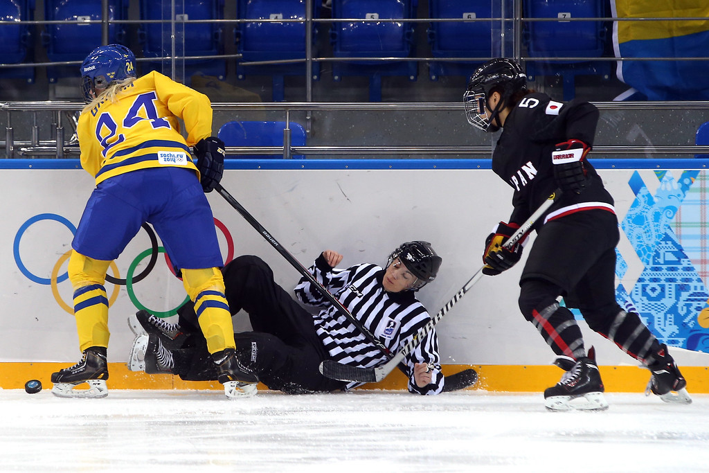 . SOCHI, RUSSIA - FEBRUARY 09: A linesman falls on the ice while Erika Grahm #24 of Sweden and Kanae Aoki #5 of Japan fight for the puck during the Women\'s Ice Hockey Preliminary Round Group B Game on day two of the Sochi 2014 Winter Olympics at Shayba Arena on February 9, 2014 in Sochi, Russia.  (Photo by Bruce Bennett/Getty Images)