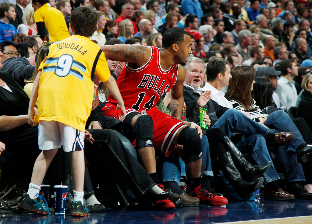 . Chicago Bulls guard Daequan Cook lands in the courtside seats while pursuing a loose ball against the Denver Nuggets in the second quarter of an NBA basketball game in Denver on Thursday, Feb. 7, 2013. (AP Photo/David Zalubowski)