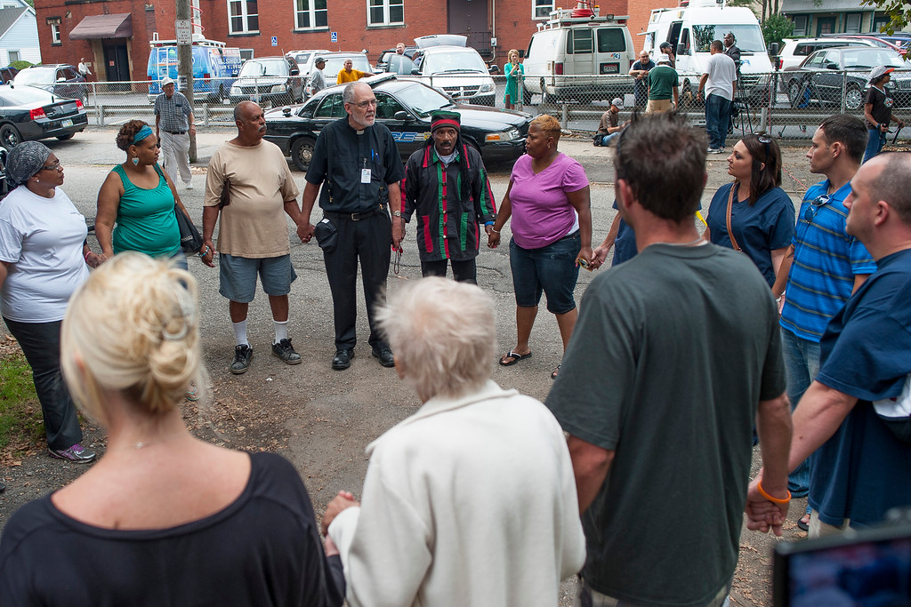. CLEVELAND, OH - AUGUST 7: Pastor Dennis Schmidt (5th L) of The Intentional Interim Ministry leads a prayer circle down the street from the home of Ariel Castro on August 7, 2013 in Cleveland, Ohio. Castro\'s home was demolished after he was found guilty of abducting three young women between 2002 and 2004. Castro, who held 3 women captive for a decade, has committed suicide, Tuesday, Sept. 3, 2013. (Photo by Angelo Merendino/Getty Images)