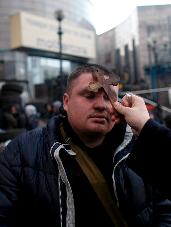 . An anti-government protester gets a blessing from a priest at Independence Square in Kiev, Ukraine, Friday, Feb. 21, 2014. Ukraine\'s presidency said Friday that it has negotiated a deal intended to end battles between police and protesters that have killed scores and injured hundreds, but European mediators involved in the talks wouldn\'t confirm a breakthrough. (AP Photo/ Marko Drobnjakovic)