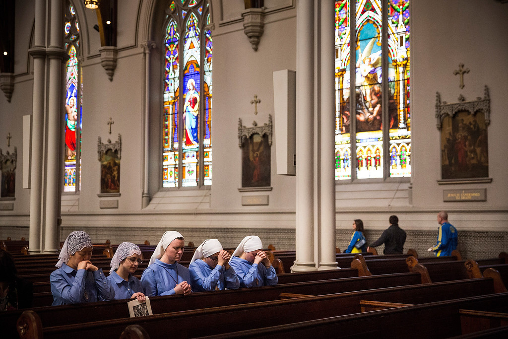 . Nuns kneel in prayer while Boston Marathon runners leave at the end of Easter Mass service at Cathedral of the Holy Cross, on April 20, 2014 in Boston, Massachusetts. This year\'s marathon will be held tomorrow, Monday, April 21; last year two pressure cooker bombs were detonated near the finish line, killing three people and injuring more than 260 others.  (Photo by Andrew Burton/Getty Images)