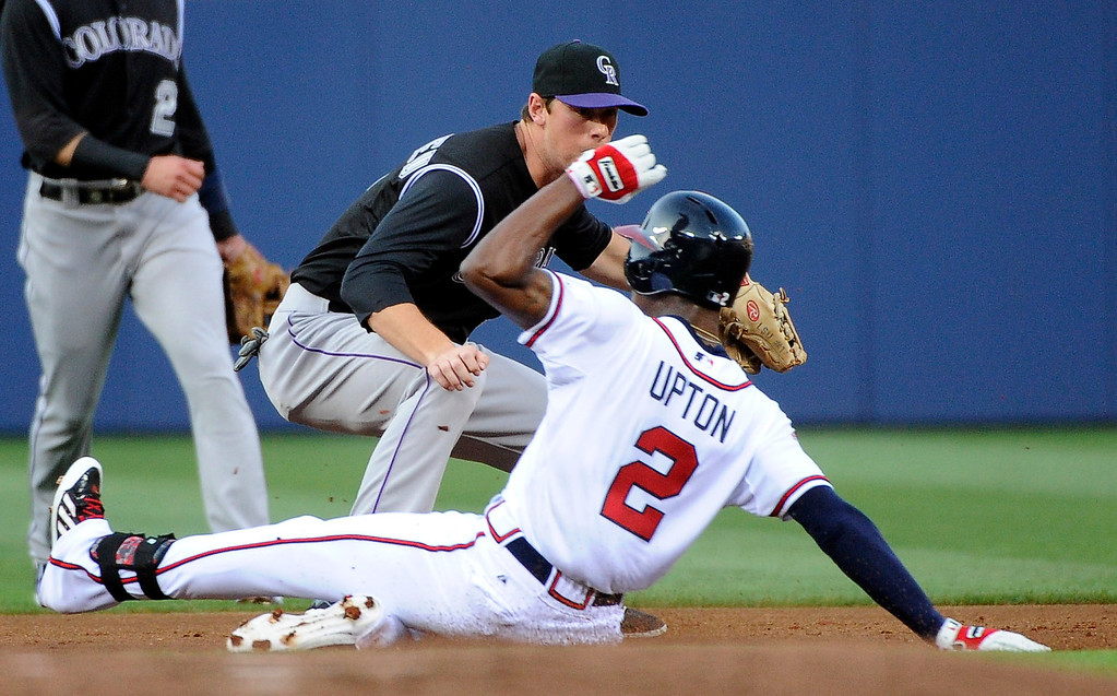 . Atlanta Braves\' B.J. Upton (2) safely slides into second base on a double as Colorado Rockies\' DJ LeMahieu turns to try to tag him during the first inning of a baseball game Friday, May 23, 2014, in Atlanta. (AP Photo/David Tulis)