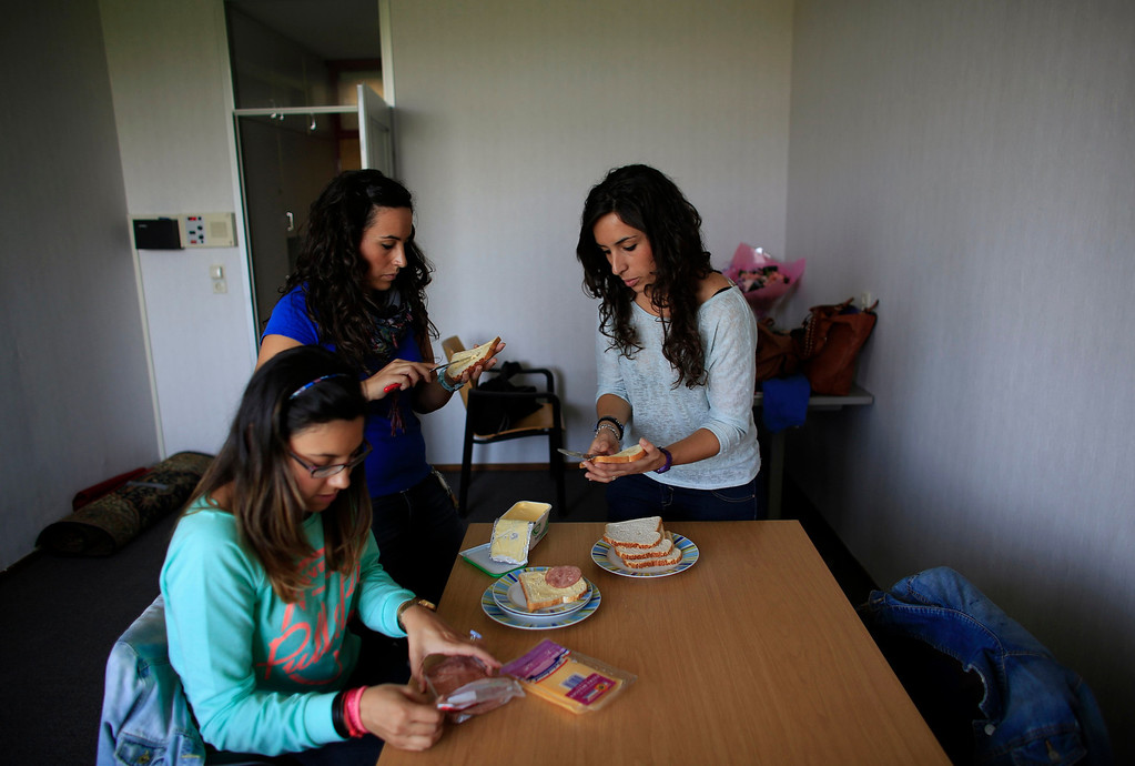 . Spanish nurses Maria Jose Marin (R), 23, and her twin sister Maria Teresa (C) make sandwiches with Sara Vallejo, 22, in their apartment in the Deo Gratias nursing home in The Hague, June 6, 2013. After months of studying Dutch, a group of young Spanish nurses moved to the Netherlands to take up work, fleeing a dismal job market at home. Spain\'s population dropped last year for the first time on record as young professionals and immigrants who moved here during a construction boom head for greener pastures. Spain\'s jobless rate is 27 percent, and more than half of young workers are unemployed. For Spanish nurses, the Netherlands\' nursing deficit is a boon. Picture taken June 6, 2013.  REUTERS/Marcelo del Pozo
