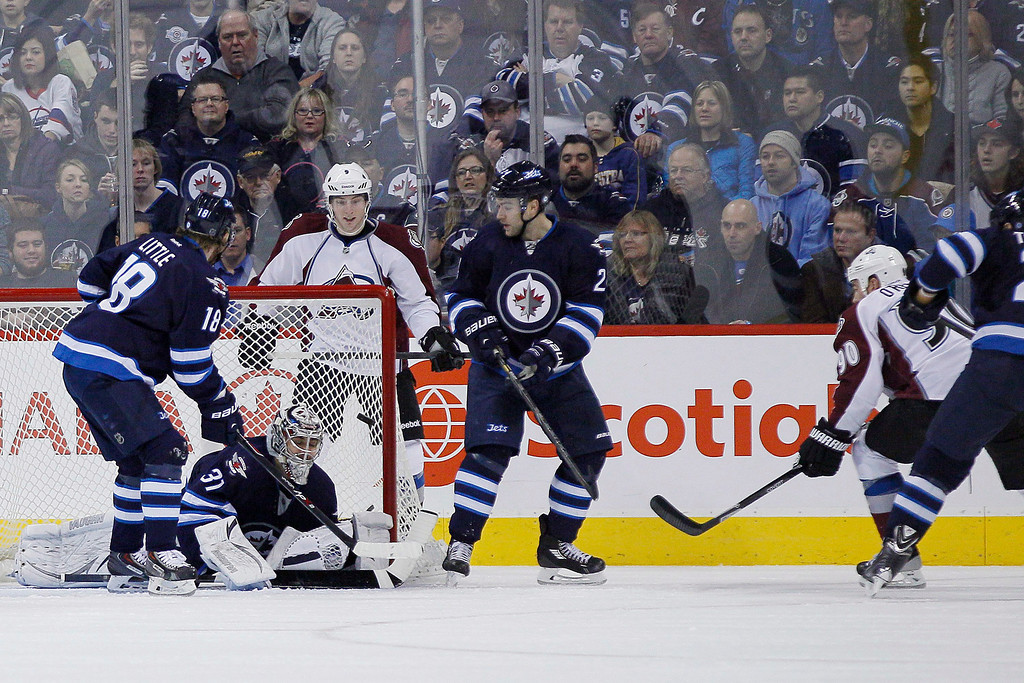 . Colorado Avalanche\'s Ryan O\'Reilly (90) scores on Winnipeg Jets\' goaltender Ondrej Pavelec (31) as Jets\' Bryan Little (18) and Grant Clitsome (24) and Avalanche\'s Matt Duchene (9) look for the rebound during second period NHL hockey action in Winnipeg, Manitoba, on Thursday, Dec. 12, 2013. (AP Photo/The Canadian Press, John Woods)
