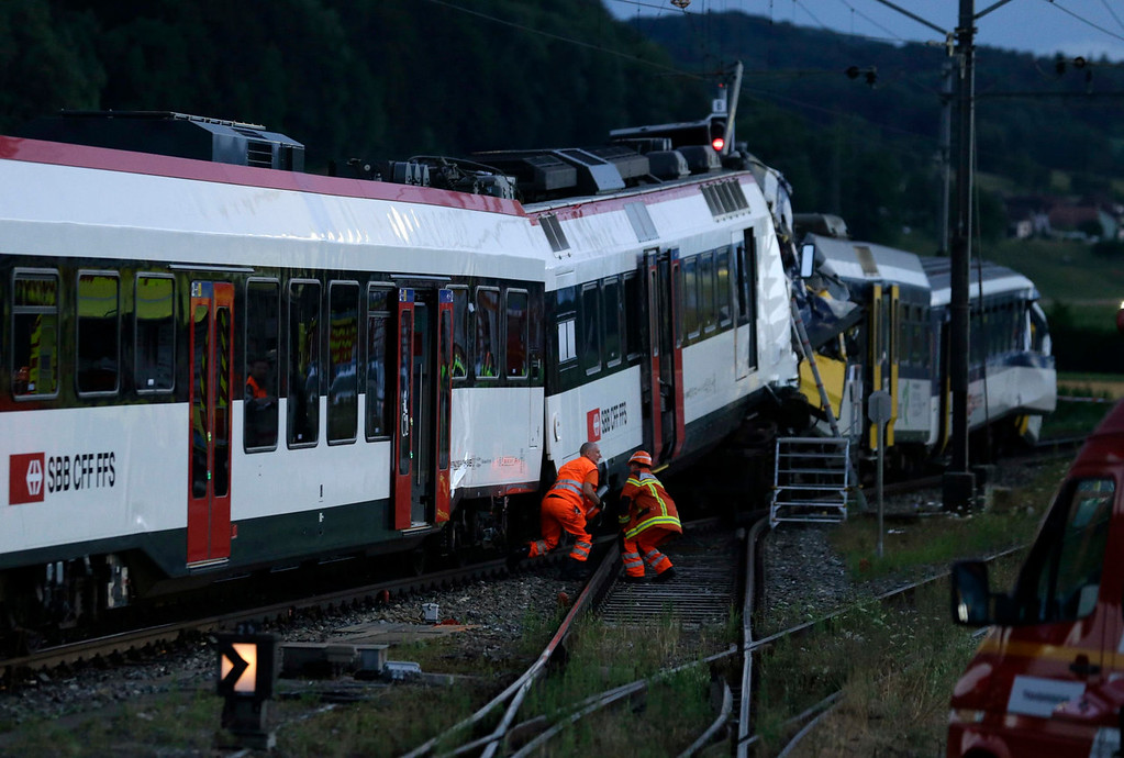 . Rescue workers are seen at the site of a head-on collision between two trains near Granges-pres-Marnand, near Payerne in western Switzerland July 29, 2013. The two trains collided in the Swiss canton of Vaud on Monday evening, injuring about 40 people, four seriously, Swiss news agency ATS reported. There was no immediate report of any deaths in the crash. REUTERS/Denis Balibouse