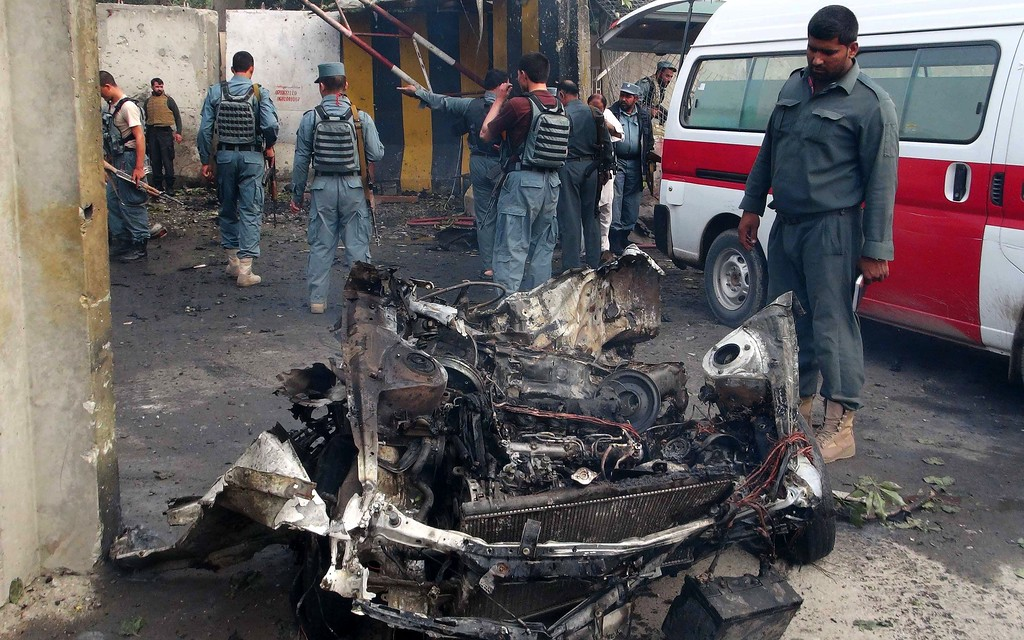 . Afghan security forces inspect the site of a suicide attack in Jalalabad on October 12, 2013.  A suicide bomber killed two policemen when he slammed an explosives-laden car into a police headquarters in east Afghanistan, underlining the country\'s instability as US Secretary of State John Kerry visited Kabul. OMAR GUL/AFP/Getty Images