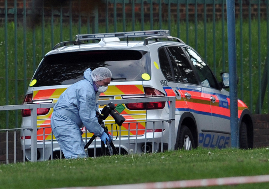 . A police forensics officer takes photographs inside a cordoned off area in Woolwich, east London, on May 22, 2013, following an incident in which one man was killed and two others seriously injured.    AFP PHOTO / CARL COURT/AFP/Getty Images