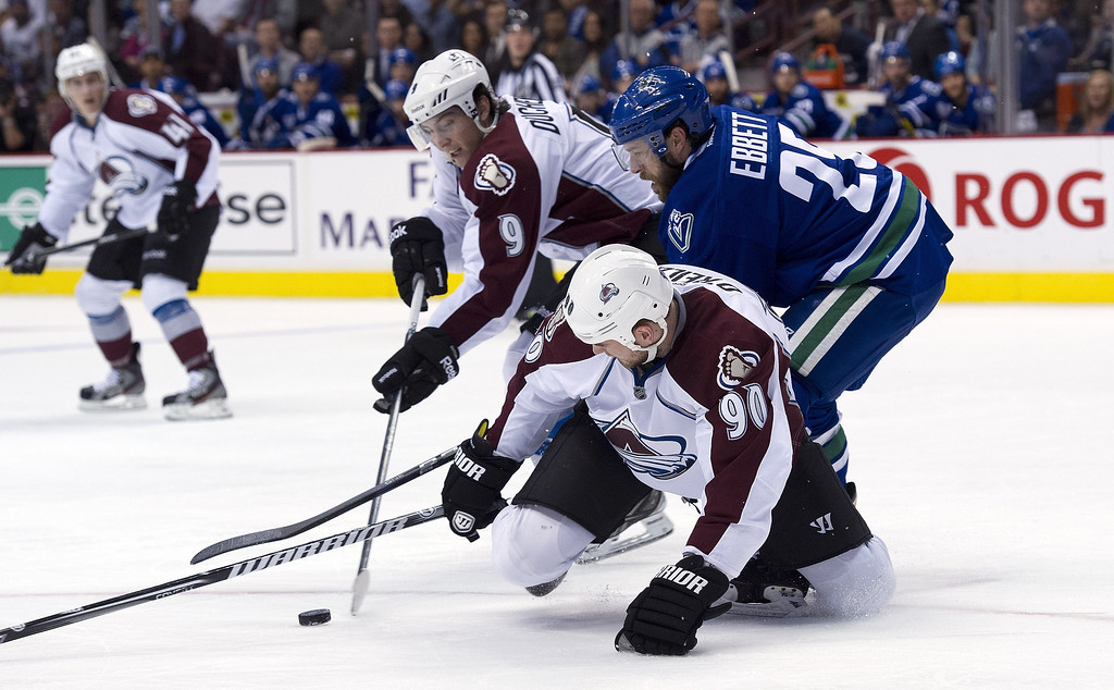 . Andrew Ebbett #25 of the Vancouver Canucks battles Matt Duchene #9 and Ryan O\'Reilly #90 of the Colorado Avalanche during the first period in NHL action on March 28, 2013 at Rogers Arena in Vancouver, British Columbia, Canada.  (Photo by Rich Lam/Getty Images)