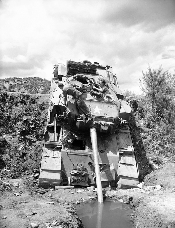 . This British Centurian tank resembles an Elephant drinking water as it rests at a crazy angle, its gun barrel sticking into a waterhole on a Korean roadside north of Seoul on June 22, 1951. Working to salvage usable parts are Lance Corp. Douglas Bone, left, of Basings, Hampshire, Eng., and Trooper Ronald Rodda, Sunderland County, Durham, Eng. (AP Photo/E.N. Johnson