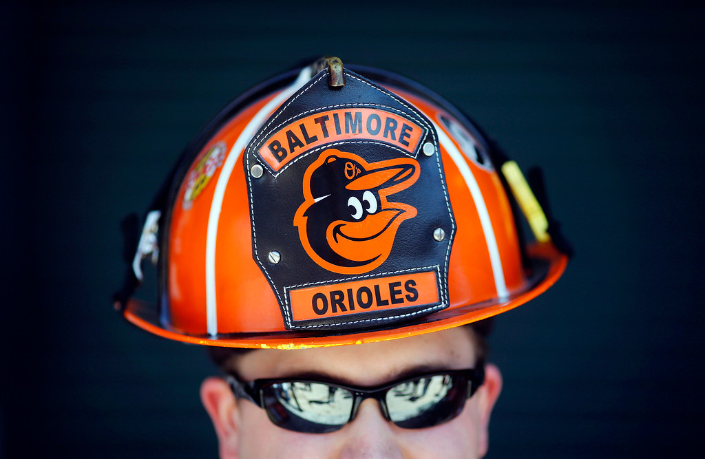 . Wes Roberts, of Whiteford, Md., poses in a Baltimore Orioles-themed fireman\'s helmet before an opening day baseball game between the Orioles and the Boston Red Sox, Monday, March 31, 2014, in Baltimore. (AP Photo/Patrick Semansky)