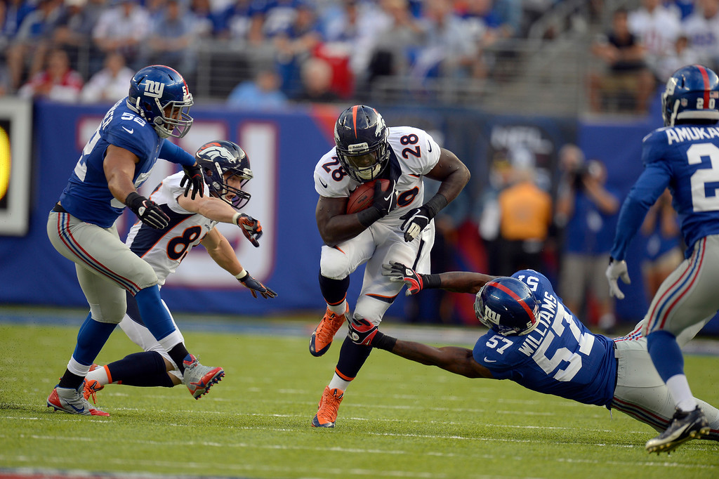 . EAST RUTHERFORD , NJ -SEPTEMBER 15: running back Montee Ball (28) of the Denver Broncos picks up a big gain after catching a pass and gets tripped up by outside linebacker Jacquian Williams (57) of the New York Giants during the first quarter September 15, 2013 MetLife Stadium. (Photo by John Leyba/The Denver Post)
