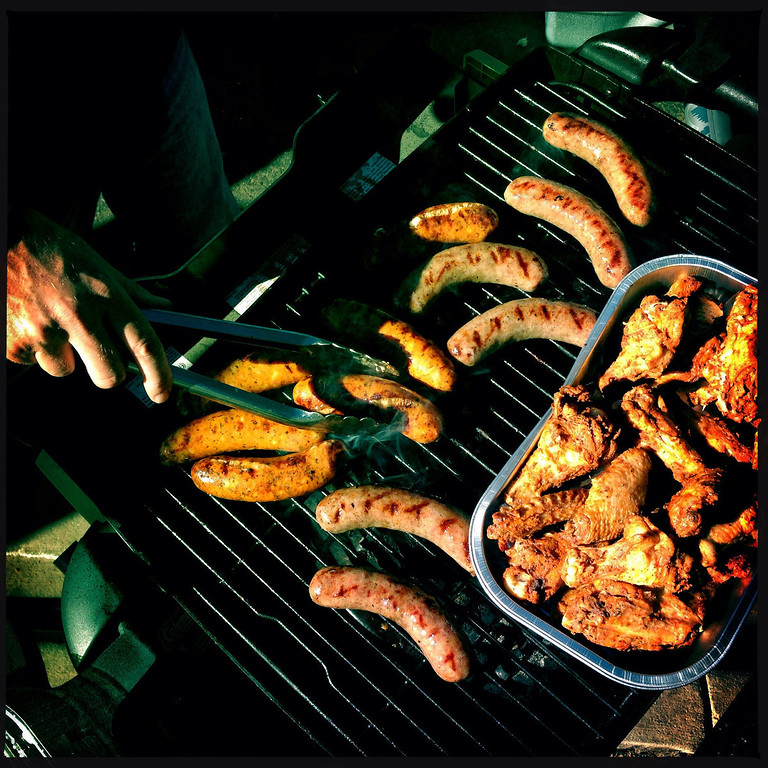 . Ross Anderson cooking chicken and brats. Photo by Craig F. Walker.