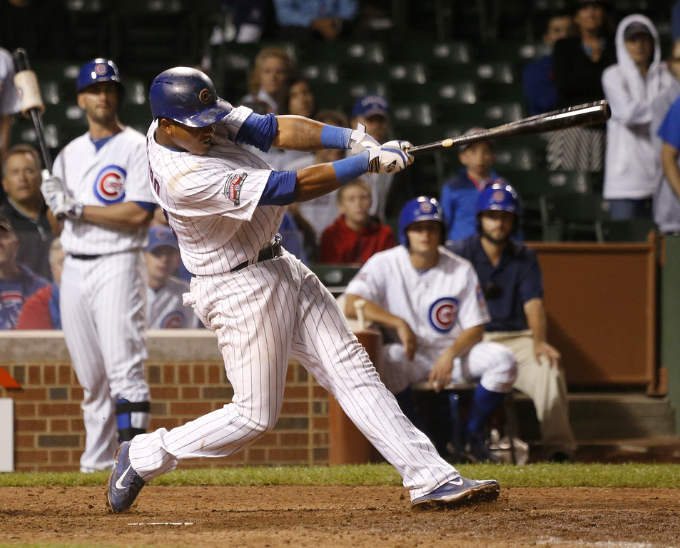 . Chicago Cubs\' Starlin Castro hits a game winning sacrifice fly off a pitch from Colorado Rockies relief pitcher Tyler Matzek, scoring John Baker, during the 16th inning of a baseball game Tuesday, July 29, 2014, in Chicago. The Cubs\' won 4-3. (AP Photo/Charles Rex Arbogast)