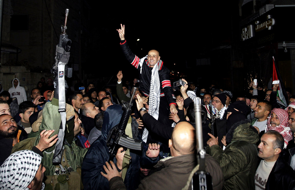 . Released Palestinian prisoner Osama al-Selawa is welcomed by relatives and militants in the West Bank city of Jenin Tuesday, Dec. 31, 2013. Israel released more than two dozen Palestinian prisoners convicted in deadly attacks against Israelis early Tuesday as part of a U.S.-brokered package to restart Mideast peace talks. (AP Photo/Mohammed Ballas)