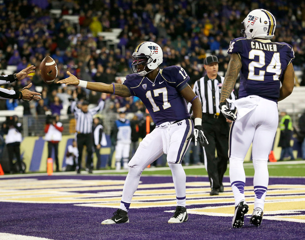 . Washington quarterback Keith Price (17) gives the ball to an official as Jesse Callier (24) looks on after Price ran for a touchdown against Colorado in the second half of an NCAA college football game on Saturday, Nov. 9, 2013, in Seattle. Washington won 59-7. (AP Photo/Ted S. Warren)