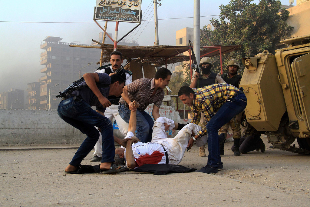. Egyptian security forces help the lifeless body of Giza Police Gen. Nabil Farrag, center, who was killed after unidentified militants opened fire on security forces deployed early morning in the town of Kerdasa, near Giza Pyramids, Egypt, Thursday, Sept. 19, 2013.  (AP Photo/Ahmed Ramadan, File)