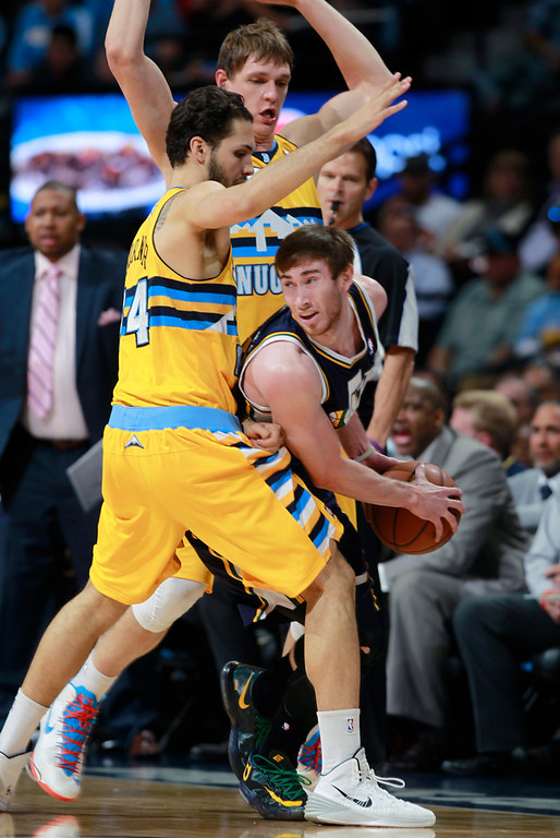 . Utah Jazz forward Gordon Hayward, front right, is trapped with the ball by Denver Nuggets guard Evan Fournier, front left, of France, and center Timofey Mozgov, back, of Russia, in the first quarter of an NBA basketball game in Denver on Saturday, April 12, 2014. (AP Photo/David Zalubowski)