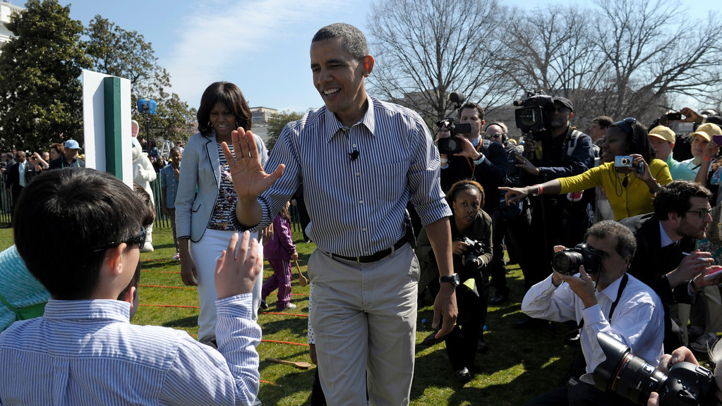 . President Barack Obama, accompanied by first lady Michelle Obama, high-fives a participant in the annual Easter Egg Roll on the South Lawn of the White House in Washington, Monday, April 1, 2013. (AP Photo/Susan Walsh)