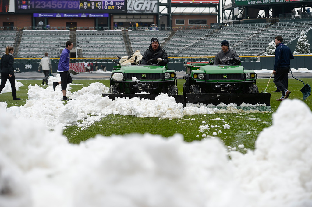 . Mark Razum (R) and Jason Garner (R) run the gators to clear snow off the right field grass after an overnight storm hit the area. Rockies grounds crew and employees work to clear the field of snow to get the first game of a double header in against the  New York Mets April 16, 2013 at Coors Field. (Photo By John Leyba/The Denver Post)