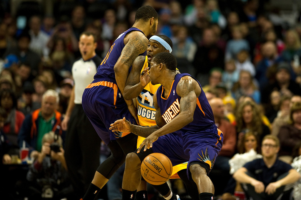 . DENVER, CO - DECEMBER 20: Ty Lawson #3 of the Denver Nuggets is squeezed between Markieff Morris #11 and Eric Bledsoe #2 of the Phoenix Suns during the first quarter of an NBA game at the Pepsi Center on December 20, 2013, in Denver, Colorado. (Photo by Daniel Petty/The Denver Post)