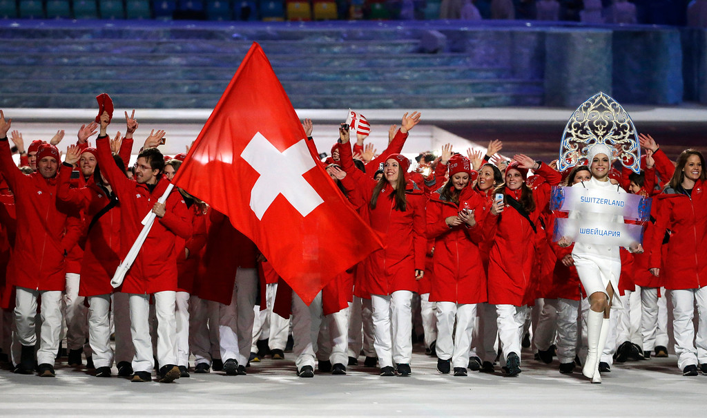 . Simon Ammann of Switzerland carries the national flag as he leads the team during the opening ceremony of the 2014 Winter Olympics in Sochi, Russia, Friday, Feb. 7, 2014. (AP Photo/Mark Humphrey)