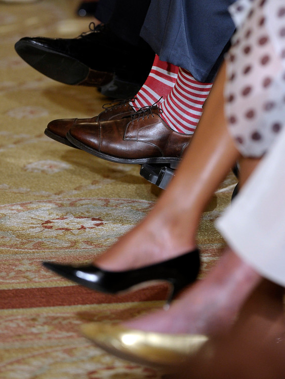 """. Former President George H. W. Bush, in a pair of red and white socks, participates in an award ceremony with President Barack Obama for the 5,000th Daily Point of Light Award ceremony in the East Room of the White House of the White House in Washington, Monday, July 15, 2013. The other shoes belong to, from top to bottom, President Barack Obama, Bush, first lady Michelle Obama and former first lady Barbara Bush. Obama welcomed Bush to the White House in a salute to public service and to the drive for volunteerism that the 41st president inspired with his \""""thousand points of light\"""" initiative more than two decades ago.  (AP Photo/Susan Walsh)"""