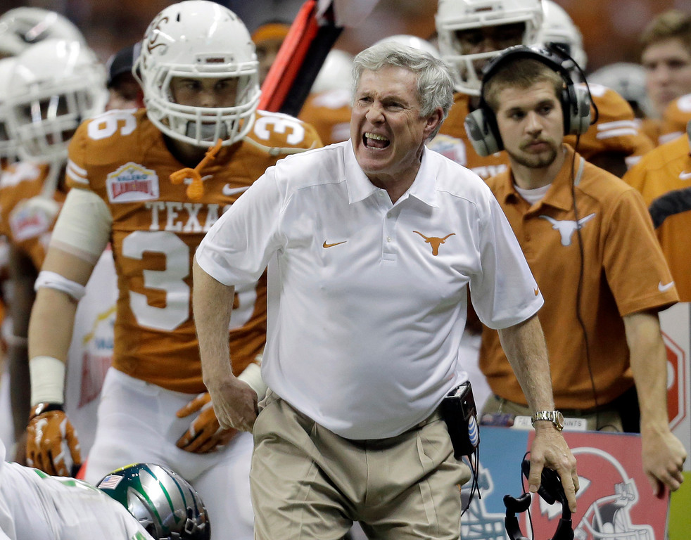 . Texas coach Mack Brown, center, argues a call during the second half of the Valero Alamo Bowl NCAA college football game against Oregon, Monday,  Dec. 30, 2013, in San Antonio. Brown has resigned and the game is his last. (AP Photo/Eric Gay)