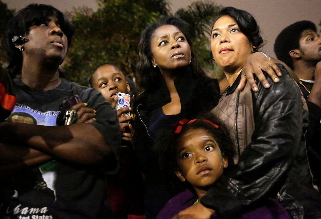 . (L-R) Debra Reid, Yanni Medina, 13, her mother Carol Medina, Blanca Zavala and her daughter J\'Len Edmund, 6, attend a rally following the George Zimmerman verdict in the Leimert Park neighborhood of Los Angeles, California July 13, 2013. A Florida jury acquitted George Zimmerman on Saturday in the shooting death of unarmed black teenager Trayvon Martin in a case that sparked a national debate over racial profiling and self-defense laws. REUTERS/Jason Redmond