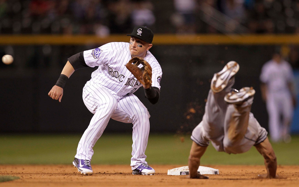 . Colorado Rockies shortstop Troy Tulowitzki, left, waits for the ball as San Diego Padres\' Will Venable dives for second base on an attempted steal in the sixth inning of a baseball game in Denver on Tuesday, Aug. 13, 2013.(AP Photo/Joe Mahoney)