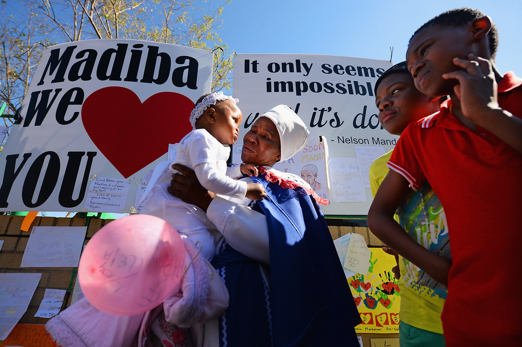 . PRETORIA, SOUTH AFRICA - JUNE 26:  People gather to leave messages of support for former South African President Nelson Mandela outside the Mediclinic Heart Hospital June 26, 2013 in Pretoria, South Africa. South African President Jacob Zuma confirmed on Sunday that Mandela\'s condition has become critical since he was admitted to the hospital over two weeks ago for a recurring lung infection.  (Photo by Jeff J Mitchell/Getty Images)