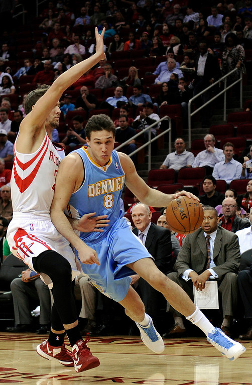 . Denver Nuggets\' Danilo Gallinari (8) drives the ball around Houston Rockets\' Chandler Parsons, left, in the first half of an NBA basketball game Wednesday, Jan. 23, 2013, in Houston. (AP Photo/Pat Sullivan)