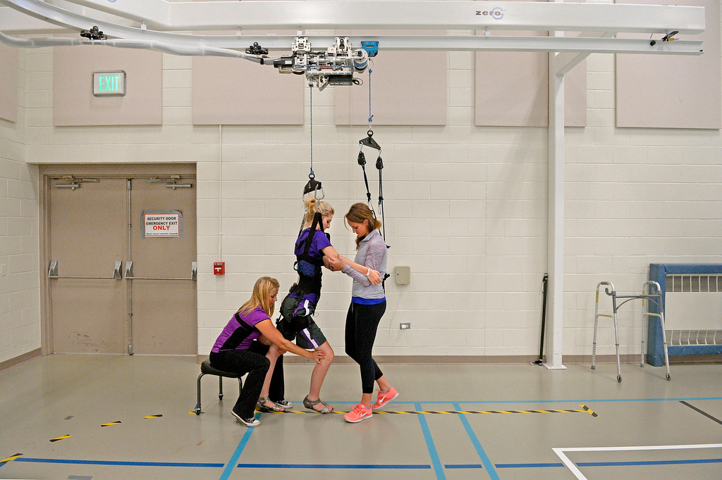 . Mackenzie Gorden works with therapists Emma Dawson, left, and Shelby Allen on a weight-support walking track, wearing a a pair of dress shoes. Mackenzie, who broke her neck when she rolled her pickup to avoid a deer, wanted to re-learn to walk under her own power by the time of her sister\'s wedding in early September. Craig Hospital has spent millions of dollars on new machinery and technology in its gym that help patients use �locomotor� training to regain walking skills. (Photo By Craig F. Walker / The Denver Post)
