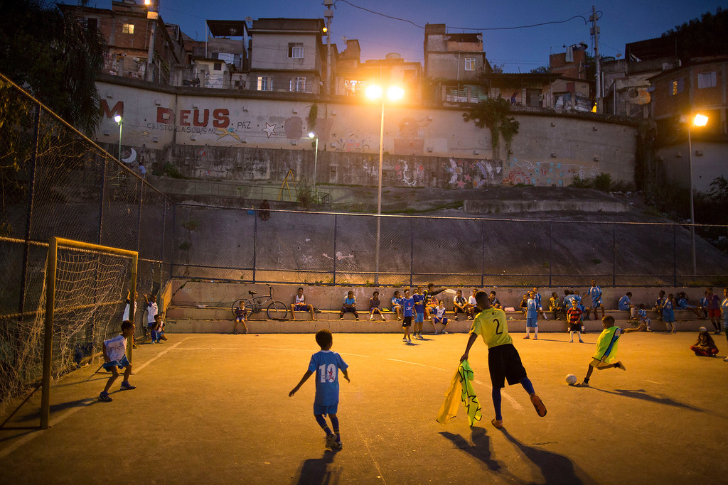 . In this Monday, June 2, 2014 photo, children attend a soccer school class on a court in the Mangueira slum of Rio de Janeiro, Brazil. The aspiring soccer stars of Rio de Janeiroís historic Mangueira slum donít have far to look for inspiration. The slum sits on a hill overlooking Brazilís temple to soccer, the fabled Maracana stadium, where legends from Pele to Neymar have played. (AP Photo/Leo Correa)