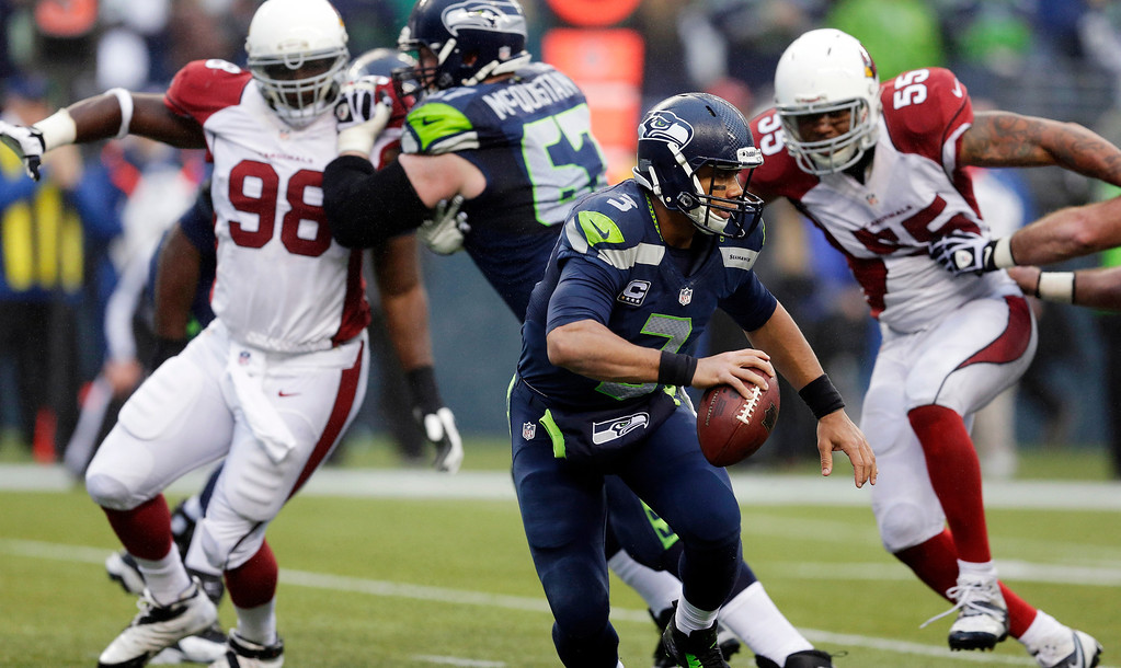 . Seattle Seahawks quarterback Russell Wilson (3) passes as Arizona Cardinals defensive end Frostee Rucker (98) and Arizona Cardinals John Abraham (55) move in on defense in the second half of an NFL football game, Sunday, Dec. 22, 2013, in Seattle. (AP Photo/Elaine Thompson)