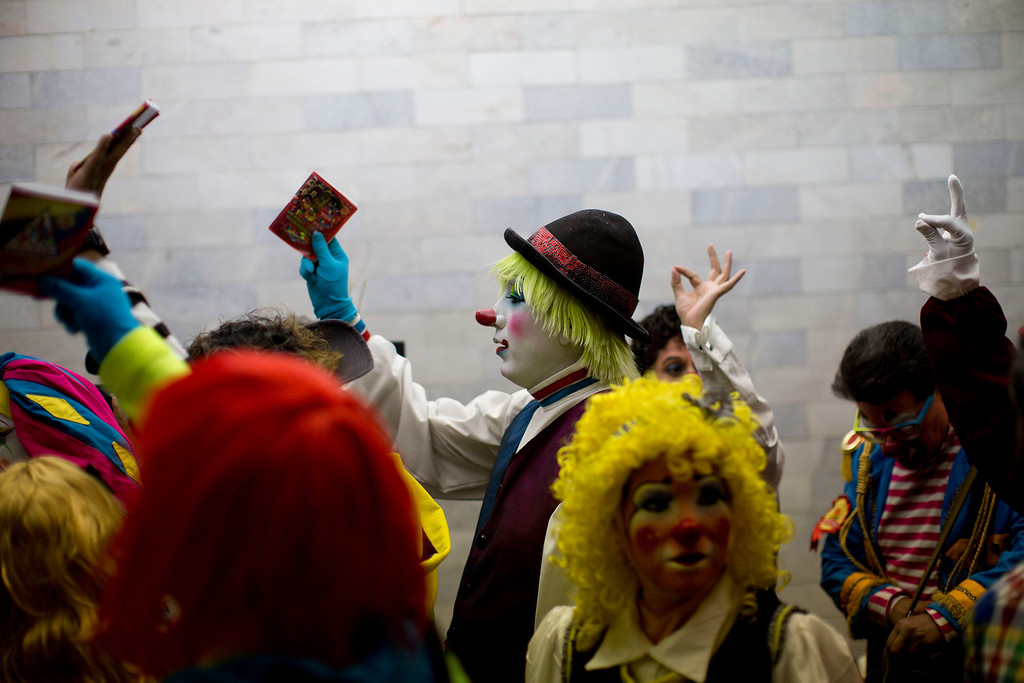 . In this Monday, Oct. 21, 2013 photo, clowns raise their official clown rule book while others without the rule book raise an imaginary one as they stand in line to register on the first day of the 17th International Clown Convention in Mexico City. The main objective of this convention is to professionalize those involved in the clown arts in Latin America and highlight the need for a School of Clown Arts in Mexico. (AP Photo/Dario Lopez-Mills)