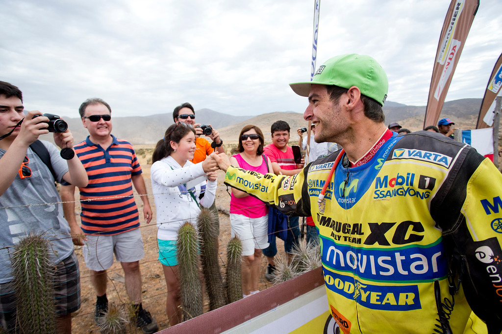 . Yamaha quad rider Ignacio Casale of Chile, right, shakes hands with fans after winning the 2014 Dakar Rally at the end of the special of the thirteenth stage in Illapel, Chile, Saturday, Jan. 18, 2014. (AP Photo/Victor R. Caivano)