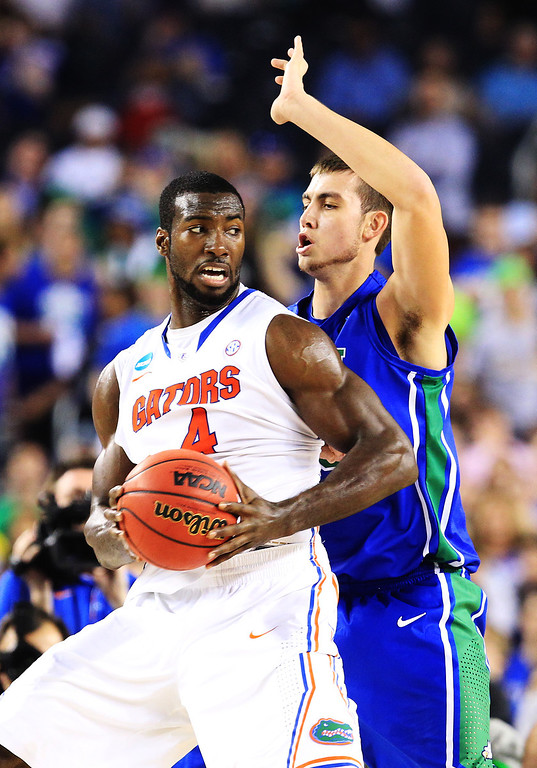 . ARLINGTON, TX - MARCH 29:  Patric Young #4 of the Florida Gators drives against Chase Fieler #20 of the Florida Gulf Coast Eagles in the first half during the South Regional Semifinal round of the 2013 NCAA Men\'s Basketball Tournament at Dallas Cowboys Stadium on March 29, 2013 in Arlington, Texas.  (Photo by Ronald Martinez/Getty Images)