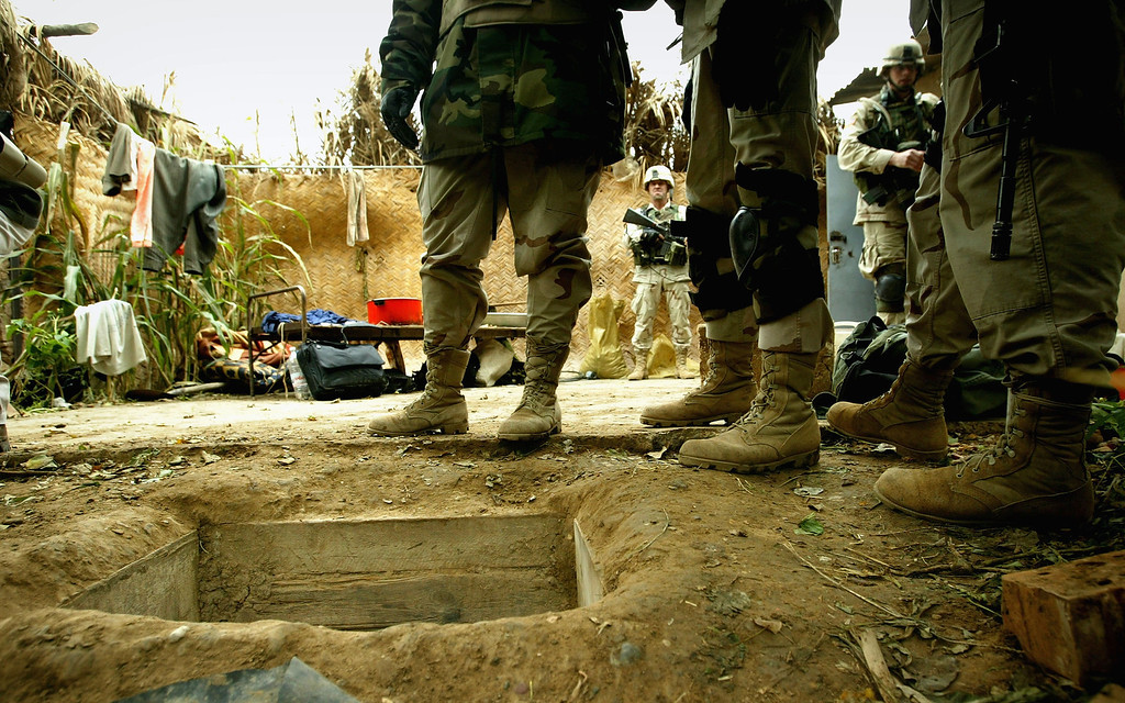 ". American soldiers in the 4th Infantry Division stand over the opening of the ""spider hole\"" where Saddam Hussein was captured December 15, 2003 in Ad Dawr, Iraq. Iraq\'s notorious dictator was captured in a raid at the compound on December 13, 2003. (Photo by Chris Hondros/Getty Images)"