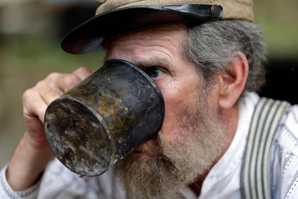 . David Dunn of Dallas, with the Confederate 9th Texas Infantry, takes a drink from his mug during ongoing activities commemorating the 150th anniversary of the Battle of Gettysburg, Thursday, June 27, 2013, in Gettysburg, Pa.  Union forces turned away a Confederate advance in the pivotal battle of the Civil War fought July 1-3, 1863, which was also the warís bloodiest conflict with more than 51,000 casualties. (AP Photo/Matt Rourke)